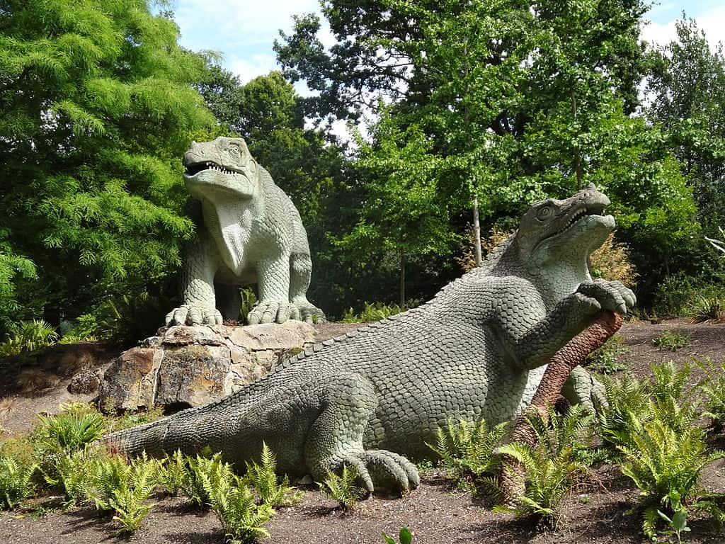 Two dinosaur statues surrounded by trees
