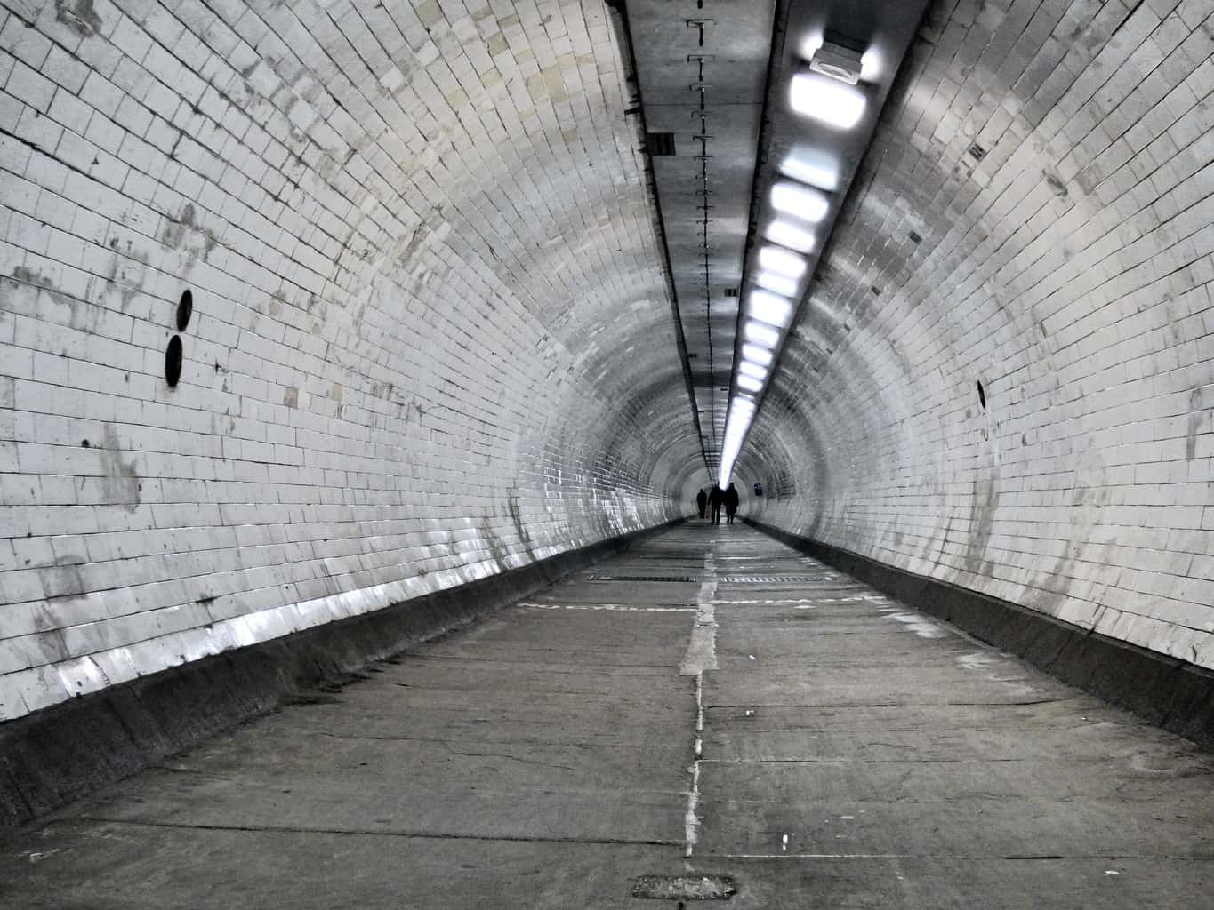 An almost empty London Underground passage with people right at the end