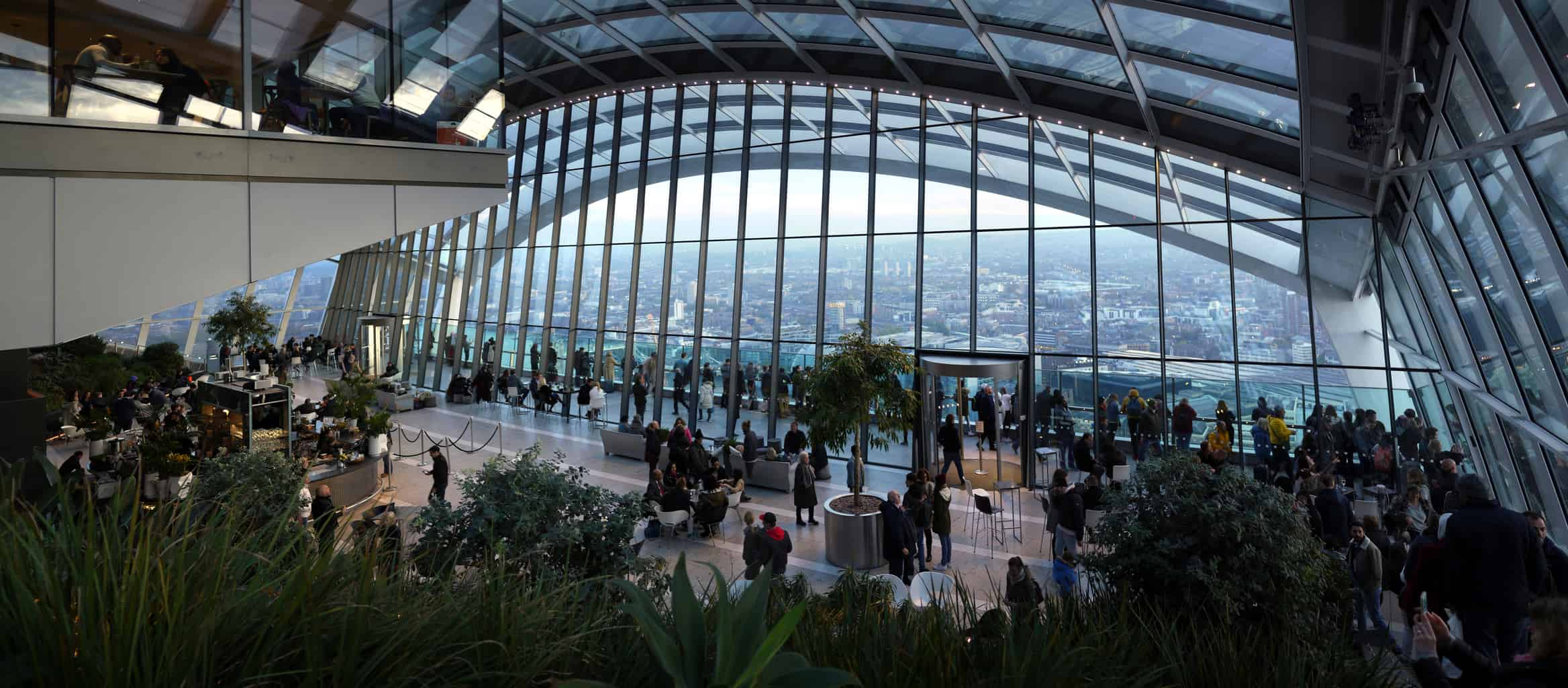"""View from inside """"Sky Garden"""" in 20 Fenchurch Street London with people milling about"""
