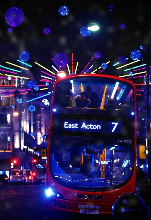 A London bus at night with neon Christmas lights behind