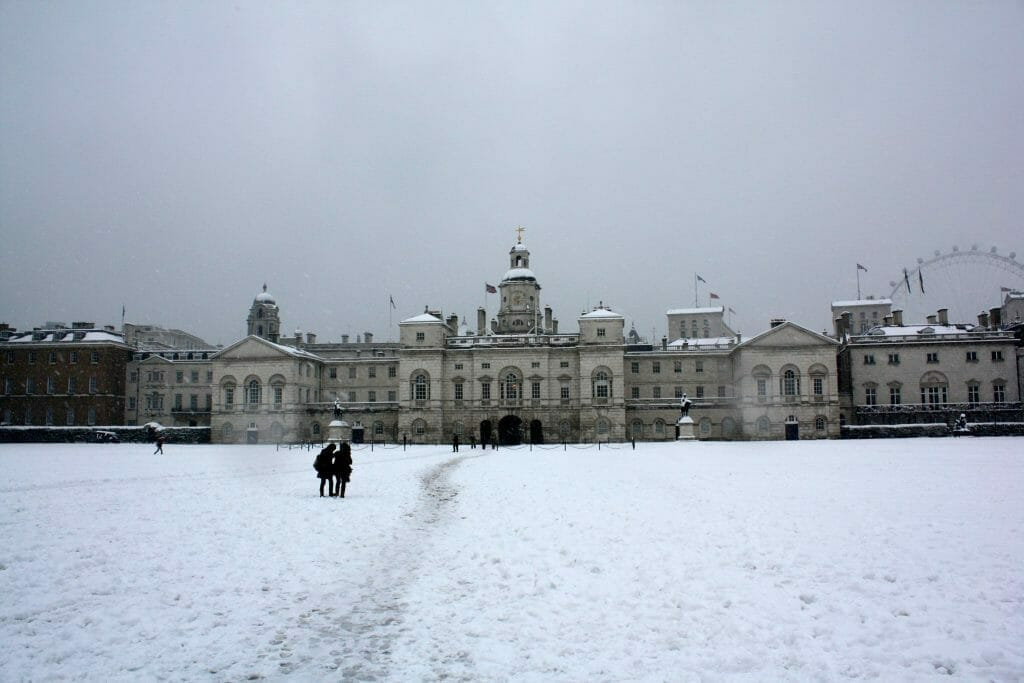 A London Palace with the London Eye in the background with snow on the ground and a grey sky