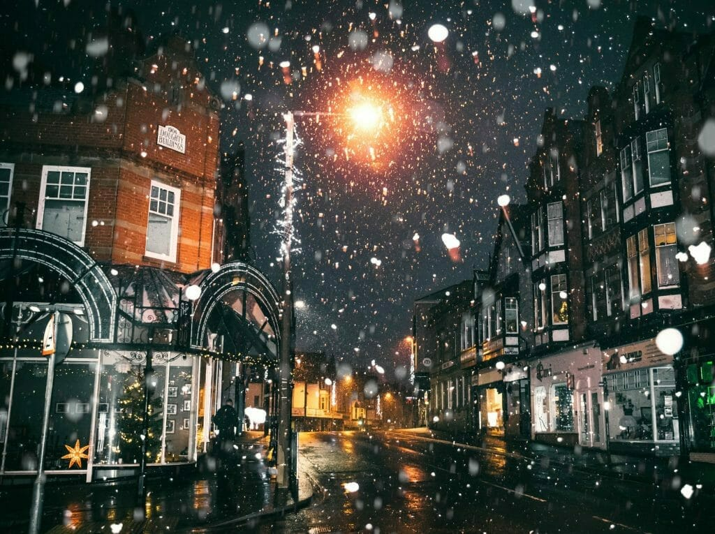 Snow coming down on a London street at night with a lamp in the background
