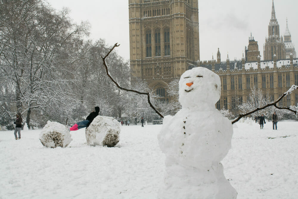 A snowman with a smile in front of Parliament, with its arms raised, with people playing in the snow behind